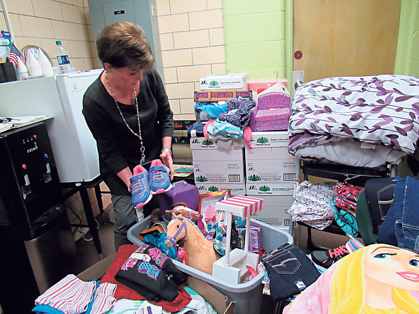 Staff photo by Cathy Spaulding<br /> Tony Goetz Elementary secretary Rhonda Wilkes packs clothing and other items donated to help three girls whose families displaced by a Saturday morning fire. People can bring donations to the school.
