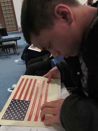 Staff photo by Cathy Spaulding<br /> Oklahoma School for the Blind student John Duong reads by running his fingers over a Braille printing of the Pledge of Allegiance. The Pledge was printed on tactile Braille American flags donated to OSB on Tuesday.