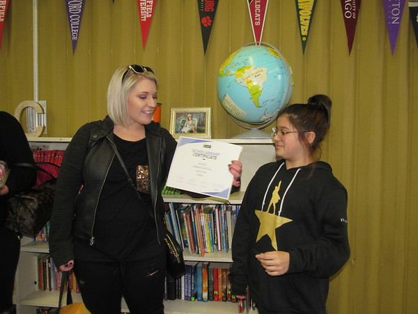 CATHY SPAULDING/Muskogee Phoenix<br /> Melissa Metzger, admissions leader for Paul Mitchell the School Tulsa, presents sixth-grader Myriah Synar with a $1,000 scholarship at the cosmetology school. The scholarship takes effect in 2026, after Myriah graduates from high school.