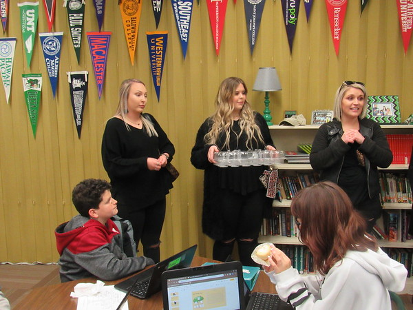 CATHY SPAULDING/Muskogee Phoenix<br /> Paul Mitchell the School Tulsa admissions leader Melissa Metzger, right, tells Sixth Grade Academy students about how the cosmetology school prepares people for a career. She is joined by cosmetology students, from left, Brooklyn Allen and Shelby Maldonado.