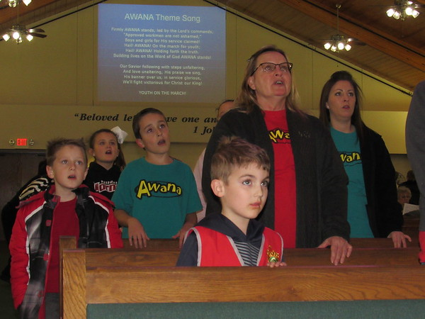 Staff photo by Cathy Spaulding<br /> Adult leaders and youth sing the Awana theme song during a recent Awana session at Southeast Baptist Church. The song is displayed on a screen in front of them, as well as behind.