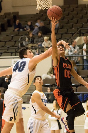 Phoenix special photo by Abigail Washington<br /> Oktaha's Tyler Baldridge extends to defend Okay's Brandon Davis, who goes up for a layup in Tuesday's opening round of the Bedouin Shrine Classic's small school divisions. Oktaha beat Okay to advance to tonight's semifinals.