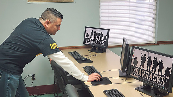 CHESLEY OXENDINE/Muskogee Phoenix<br /> Victor Lezama turns on the computers in the newly furnished computer lab at The Barracks. The veterans' center will have computers available for veterans to do research, apply for jobs, and more.