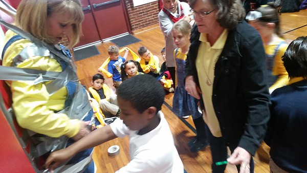 St. Joseph Catholic School second-grader Alex Yosef secures his duct tape while doing his part to tape Principal Joanne Myers to the gym wall. Students who reached reading goals got to do the taping.
