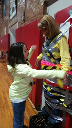 Third-grader Juliana Hutchins adds her tape to secure Principal Joanne Myers to the gymnasium wall. Students selected their favorite color of duct tape to add.