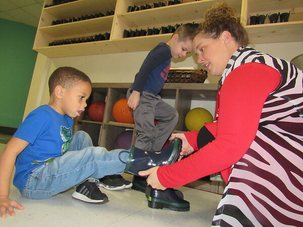 CATHY SPAULDING/Muskogee Phoenix<br /> Early Childhood Center teacher Angie Ragsdale fits a muck boot on Josiah Buchanan, left, while classmate Zane Lloyd watches. An Education Foundation of Muskogee grant funded purchase of 60 muck boots.
