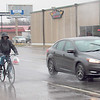 A cyclist weathers the rain while heading along North Main Street on Thursday.