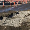 Staff photo by Mike Elswick<br /> A large hole on Okmulgee Avenue at Main Street remained Thursday after city public service crews worked overnight repairing a ruptured 8-inch water line, said Greg Riley, city public works director. The water line break left an icy sheet along Main and Okmulgee Wednesday night and early Thursday as temperatures dipped into the low 20-degree range. In addition to repairing the water line city crews were also busy sanding and salting streets. Riley said crews responded to five water line breaks on Wednesday and several more on Thursday.