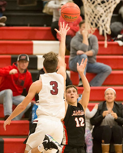 VON CASTOR/Phoenix Special Photo Hilldale's Brayson Lawson shoots a 3-point basket over the reach of Wagoner's Sawyer Jones for the game-winner to lift the Hornets over the Bulldogs Friday in Wagoner.