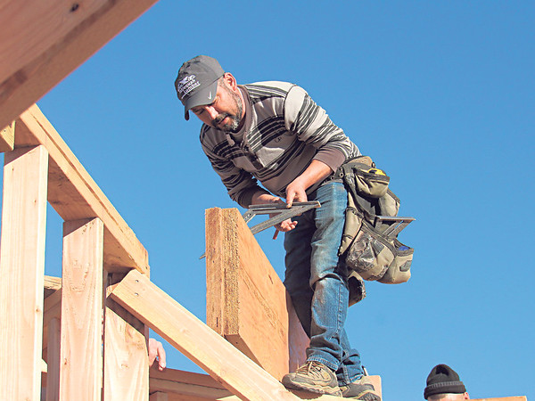 CATHY SPAULDING/Muskogee Phoenix<br /> Jaime Gonzales prepares to measure beams on a house he's helping to build. Builders spent Friday afternoon doing frame work on a home under construction in the Country Club area.
