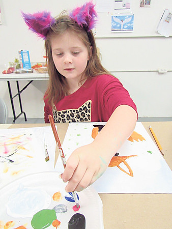 "CATHY SPAULDING/Muskogee Phoenix<br /> Robin Philbin, 8, mixes red and white paint to get the ""perfect"" shade of pink during Saturday's Young Artist painting class."