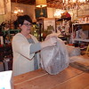 """Stacy Burns wraps a lamp in bubble wrap while waiting on a customer. She said owning a business requires """"never-ending hours."""""""