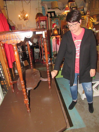 Stacy Burns shows two old tables she plans to refinish<br /> or repaint. She said one table needs to be sanded down and repainted. Another needs minor repair, but is in pretty good condition.
