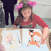 Robin Philbin, 8, concentrates on filling a fox's ears with pink.