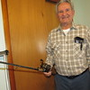Staff photo by Cathy Spaulding<br /> Billy Smith shows one of hundreds of rods and reels he keeps at his house. He says anytime is a good time to fish.