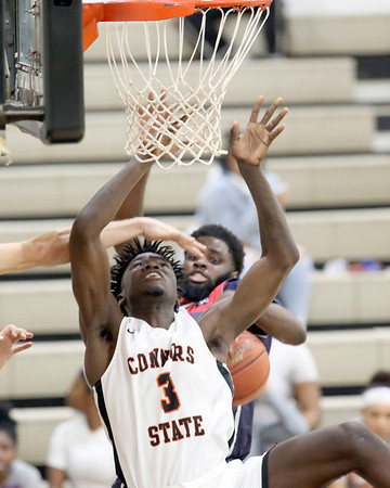 VON CASTOR/Special to the Phoenix<br /> Connors' Daylon Tanksley is fouled in the lane by Seminole State's Elijah Diouf Monday night at Melvin Self Field House in Warner. The Cowboys lost 75-67 while the Cowgirls won 65-60.
