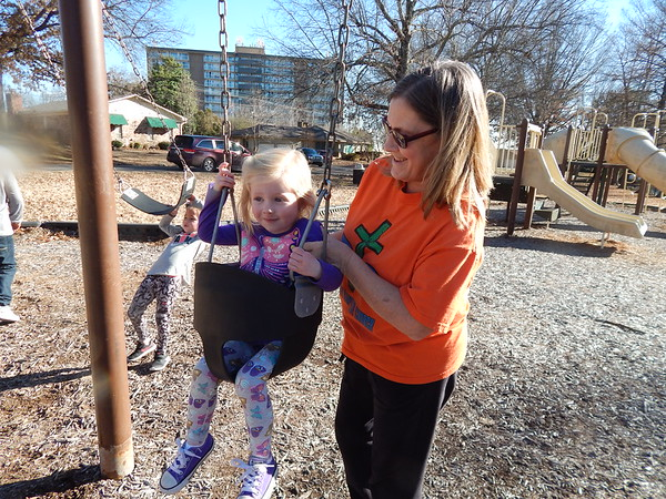 KENTON BROOKS/Muskogee Phoenix<br /> Vicki Milne, right, loads granddaughter Hayden Sandersfield, 3, into a swing at Palmer Park on Monday. Vicki's other granddaughter, 4-year-old Harper, is also on the swings as the three enjoyed the warmer and sunnier weather.