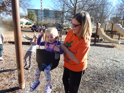 KENTON BROOKS/Muskogee Phoenix Vicki Milne, right, loads granddaughter Hayden Sandersfield, 3, into a swing at Palmer Park on Monday. Vicki's other granddaughter, 4-year-old Harper, is also on the swings as the three enjoyed the warmer and sunnier weather.