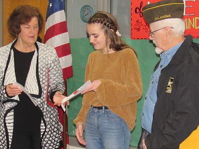 CATHY SPAULDING/Muskogee Phoenix  Veterans of Foreign Wars Post 474 Auxiliary President Sandi Stafford presents Fort Gibson eighth-grader Savannah Bebo a certificate for placing second in the district VFW Patriot's Pen essay contest. VFW Post 474 Commander Dennis Morton watches.