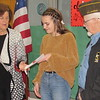 CATHY SPAULDING/Muskogee Phoenix<br /> <br /> Veterans of Foreign Wars Post 474 Auxiliary President Sandi Stafford presents Fort Gibson eighth-grader Savannah Bebo a certificate for placing second in the district VFW Patriot's Pen essay contest. VFW Post 474 Commander Dennis Morton watches.