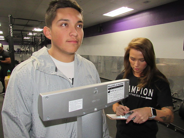 CATHY SPAULDING/Muskogee Phoenix<br /> Above: Gabriel Rojas waits on a scale while fitness nutrition specialist Selena Williams jots down his weight during the<br /> Monday weigh-in for the Champion Fitness Weight Loss Challenge.