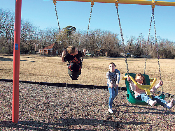 Peyton Stewart, 10, works twice as hard to push both her siblings — Aiden, 9, left, and Mia, 7 — in swings at Robison Park.