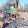 CATHY SPAULDING/Muskogee Phoenix<br /> Jacob Ireland scoops concrete in a hole after city crews repaired a water leak on Tuesday. A City of Muskogee work crew fixed a leak near the intersection of C and Houston streets.