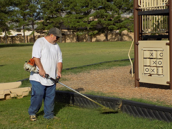 Staff photo by Mike Elswick<br /> City of Muskogee Parks and Recreation worker Leslie Lehr was busy Wednesday morning trimming around playground equipment at the city's Love-Hatbox Sports Complex.