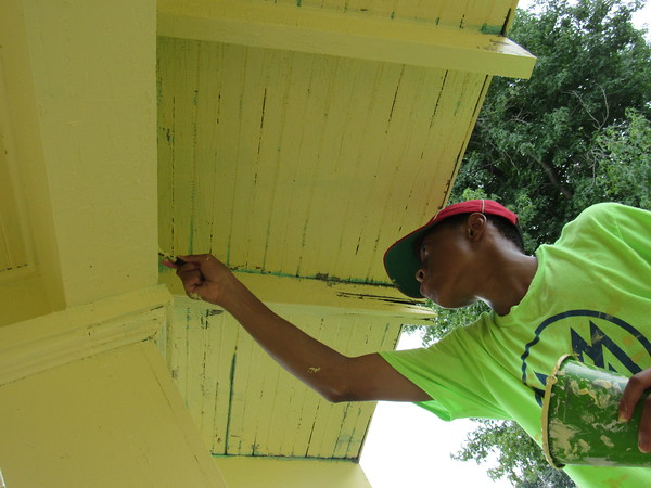 CATHY SPAULDING/Muskogee Phoenix<br /> Re'Sean Adams paints under an eave as part of Mission Muskogee.