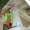 CATHY SPAULDING/Muskogee Phoenix<br /> Jordan Webster of Boulevard Christian Church braces against a column as she paints a front porch eave Monday morning. She was among more than 200 youths participating in Mission Muskogee.