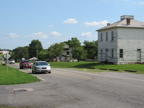 Staff photo by Cathy Spaulding<br /> Cars pass the Fort Gibson Historic Site's hospital building on Garrison Avenue. A master plan calls for sidewalks along Garrison leading to the site.