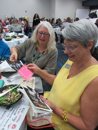 CATHY SPAULDING/Muskogee Phoenix<br /> Sue Harris, left, and Renee Fredrick look at old pictures during Wednesday's Women's Leadership Conference. The two helped organize the original Women's Leadership Conference in 2004.