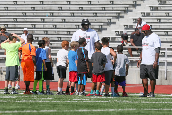 Special photo by Von Castor<br /> Former Muskogee Rougher Stacy McGee, center, and Fort Gibson defensive coordinator Kenyatta Wright, right, give instructions to a group of fifth-graders on Saturday on Creek Nation Field at Indian Bowl. McGee and former MHS teammate Robert Thomas were part of the FCA's Day of Champions camp.