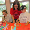 Staff photo by Cathy Spaulding<br /> Q.B. Boydstun Librarian Judy Walker, center, helps Cruz Cox, 5, make a paper football while Araya Cox, 11, folds hers.