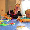 Staff photo by Cathy Spaulding<br /> Molly Martinez, 14, helps a youngster flip a paper football through a straw goal during a Thursday craft session at Q.B. Boydstun Library.