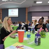 Staff photo by Cathy Spaulding<br /> Taylor Bates of FIRSTAR Bank, left, visits with Diana Diggs, office manager for the Prince Hall Masonic Lodge, during the Greater Muskogee Area Women's Leadership Conference on Wednesday. During the conference luncheon, participants were encouraged to ask each other questions printed on their placemats.