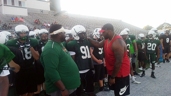 Phoenix staff photo by Mike Kays<br /> Muskogee grad and New York Giant Robert Thomas, right, talks with Rougher players during Thursday's final day of team camp on Creek Nation Field at Indian Bowl.