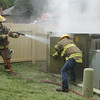 Staff photo by Harrison Grimwood<br /> Firefighter Blake Weldon sprays suppressant into a platform transformer while an OG&E serviceman opens its door. The transformer caught fire Thursday afternoon following a severe thunderstorm.