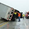 Staff photo by Harrison Grimwood<br /> Towing and recovery workers prepare to right a tractor-trailer rig that was knocked over Thursday by harsh winds on the Arkansas River bridge on U.S. 62.
