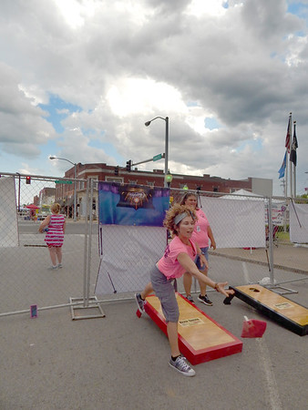 KENTON BROOKS/Muskogee Phoenix<br /> Heather Youree, left, tosses a bean bag while she and Kristy Ferrell play Cornhole during the early part of the Switch Monkey Music Festival on North Main Street in Wagoner on Saturday.