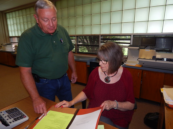 KENTON BROOKS/Muskogee Phoenix<br /> Monte Madewell, interim superintendent of Checotah Public Schools, talks over paperwork with secretary Carol Beaver. Madewell, formerly superintendent at Warner, has been on his current job since April.