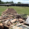Staff photo by Mark Hughes<br /> Cedar shake shingles were ripped from buildings at the Fort Gibson stockade.