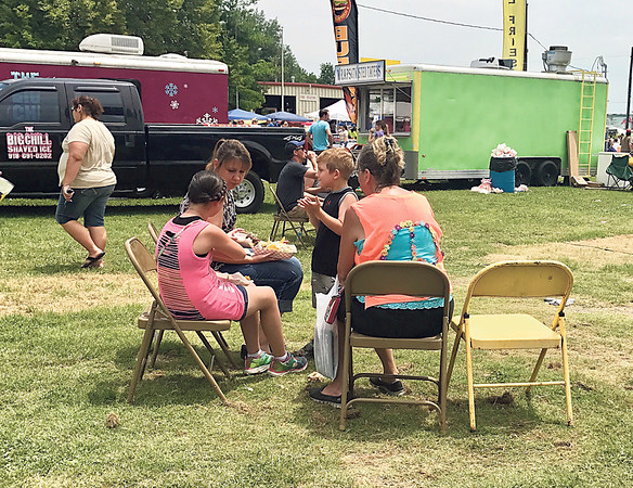 "Special photo by Travis Sloat<br /> Nellie ""Nana"" Harmon (right), Trenton Bean, Trina Bean and Breanna Wolfe all sat down to enjoy a sampling of food from the different vendors at the 2017 Porter Peach Festival on Saturday. Harmon said she's lived in Muskogee and Wagoner her entire life, but this is the first time she's come to the festival, which routinely attracts over 15,000 people a year."