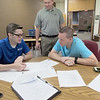CATHY SPAULDING/Muskogee Phoenix<br /> Fort Gibson School Superintendent Scott Farmer, center, checks up on a discussion between Beasley Technology representative Josh Duvall, left and District Technology Director Jason Wicks. Fort Gibson is rolling out Chromebook devices for students this semester.