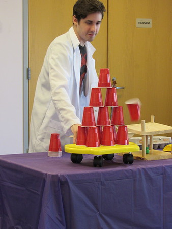 Staff photo by Cathy Spaulding<br /> One cup falls from an otherwise stable stack as Nick Gathman of Mad Science moves a cart. Gathman demonstrated structural stability at Q.B. Boydstun Library.