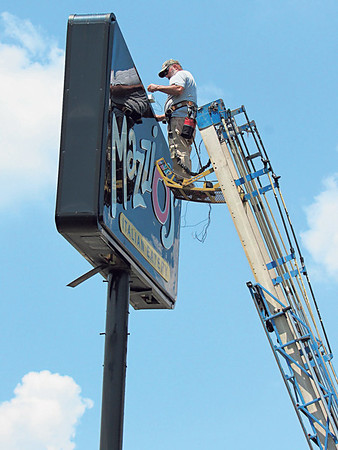 Staff photo by Cathy Spaulding<br /> A worker on an Alpha Neon ladder truck does electrical work atop a sign on East Shawnee Bypass on Monday. Calm skies enabled people to work outdoors. Temperatures this week are predicted to be in the upper 90s, according to accuweather.com.