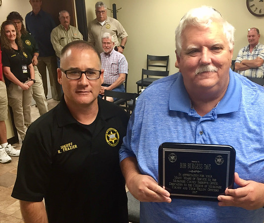 Staff photo by D.E. Smoot<br /> District 1 Road Administrator Bob Burgess, right, displays a plaque recognizing 20 years of volunteer service with the Muskogee County Sheriff's Patrol, which was presented Monday by Muskogee County Sheriff Rob Frazier, left, during a county commissioner meeting.