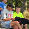 Staff photo by Cathy Spaulding<br /> First United Methodist Church member Andrea Fleming, left, shares a music book with Boy Scout Sterling Lewis, 10, while Billy Cooper uses his own music book during a Sunday worship at Greenleaf State Park. Sunday services run through Labor Day.