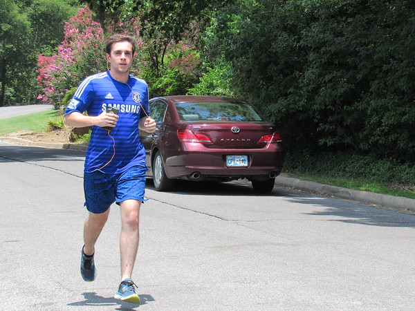 "Staff photo by Cathy Spaulding<br /> Ty Derouen passes a car while jogging in Honor Heights Park on Tuesday afternoon. Derouen, who lives in the Honor Heights neighborhood, said he jogs two or three miles each day. He said he jogs down Agency Hill first and does the ""hard part"" on the way back."