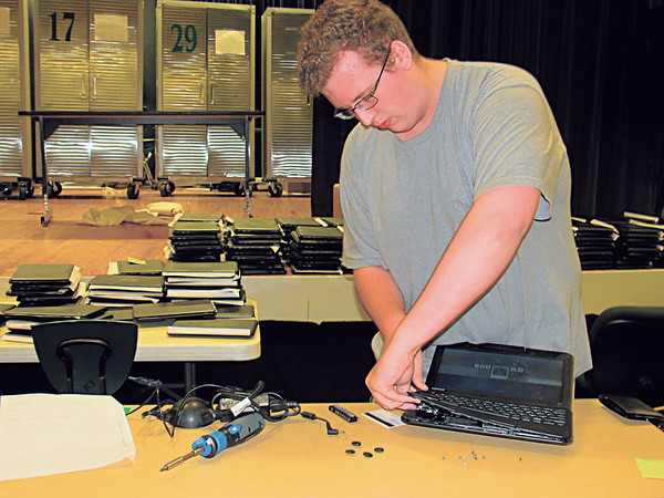 Staff photo by Cathy Spaulding<br /> Muskogee High School graduate Nathan Brock takes apart a keyboard to work on a laptop. He earned on-the-job training through the MHS computer repair program.
